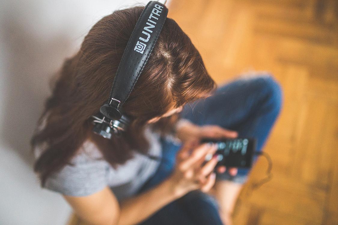 ヘッドホンやイヤホンで音楽を聴いている人々